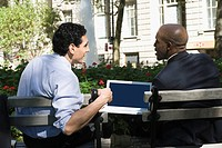 Rear view of two businessmen sitting in a park (thumbnail)
