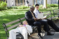 Businesswoman sleeping on a bench with two businessmen sitting beside her and looking at a laptop