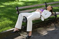 Businesswoman sleeping on a bench in a park (thumbnail)