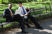 Two businessmen sitting on a bench in a park and looking at a laptop