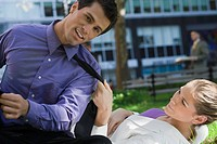 Businesswoman lying on grass and pulling the tie of a businessman