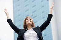 Close_up of a businesswoman smiling with her arms raised