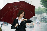 Businesswoman checking the time during rain