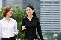 Two businesswomen walking together and smiling