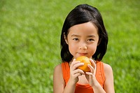 Portrait of a girl holding an orange