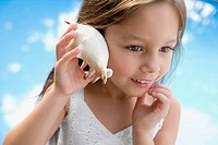 Close_up of a girl holding a seashell close to her ear
