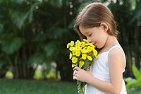 Side profile of a girl holding a bunch of flowers and smelling