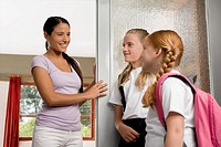 Two schoolgirls with a female teacher looking at each other and smiling