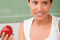 Close_up of a female teacher holding an apple and smiling