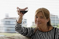 Portrait of a senior woman toasting with a wine glass