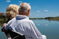 Senior couple sitting on a bench at the lakeside (thumbnail)