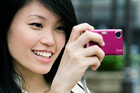 Close_up of a young woman taking a picture with a digital camera