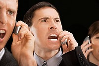Close_up of business executives shouting on mobile phones