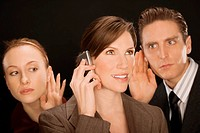 Businesswoman talking on a mobile phone with two business executives listening to her
