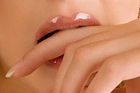 Close_up of a young woman biting her finger