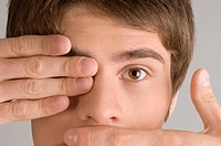 Close_up of a young man covering his mouth and his eye with his hands