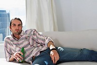 Portrait of a young man lying on a couch and holding a beer bottle
