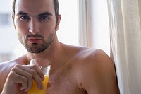 Portrait of a young man holding a glass of juice and thinking