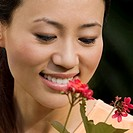 Close_up of a young woman looking at a flower and smiling