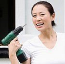 Portrait of a young woman holding a hand drill and smiling (thumbnail)