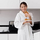 Portrait of a young woman eating croissant in the kitchen (thumbnail)