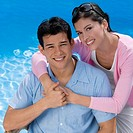 Portrait of a young couple smiling at the poolside (thumbnail)