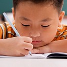 Close_up of a schoolboy writing on a notebook with a pencil