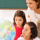 Two schoolgirls with a female teacher looking at a globe