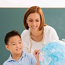 Close_up of a schoolboy with his teacher looking at a globe and smiling