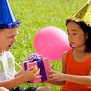 Close-up of a boy giving a birthday present to a girl (thumbnail)