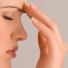 Close-up of a young woman touching her forehead (thumbnail)