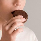 Close_up of a young woman eating a cookie