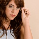 Close_up of a young woman adjusting her eyeglasses