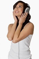 Close_up of a young woman listening to music with headphones and smiling