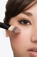 Close_up of a young woman applying make_up