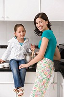 Portrait of a young woman smiling with her daughter in a kitchen