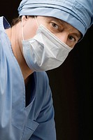 Close_up of a surgeon wearing scrubs and a surgical mask