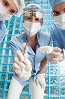 Two female surgeons and a male surgeon in an operating room (thumbnail)