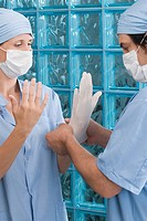 Male surgeon adjusting a surgical glove of a female surgeon (thumbnail)