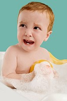 Close_up of a boy sitting in a bathtub and crying
