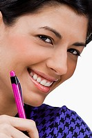 Portrait of a young woman holding a pen and smiling