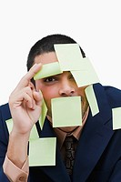 Portrait of a businessman covered with adhesive notes