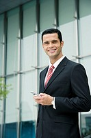 Portrait of a businessman holding a mobile phone and smiling
