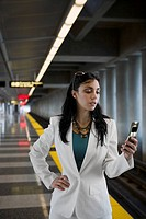 Businesswoman text messaging on a mobile phone at a subway station