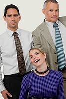 Close_up of a businesswoman laughing with two businessmen standing behind her