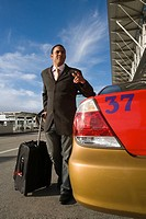 Businessman standing near a taxi with holding his luggage and gesturing