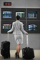 Rear view of a businesswoman standing with her luggage in front of an arrival departure board at an airport