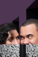 Close_up of a young couple hiding their face with a textbook