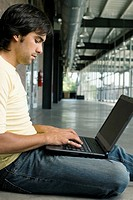 Side profile of a young man working on a laptop (thumbnail)