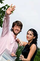 Young man waving hand with a young woman standing beside him